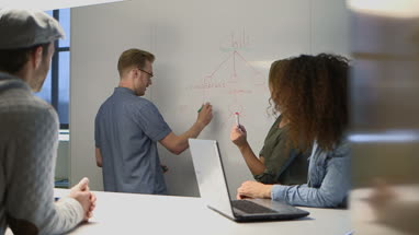 Businessman writing on whiteboard while discussing with another business people