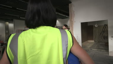Men and woman discussing at construction site