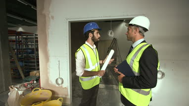 Male architect discussing at construction site