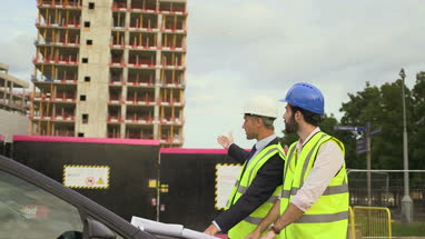 Male architect discussing with blueprint at construction site