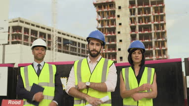 Men and woman looking at camera confidently at construction site