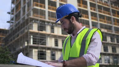 Male architect looking blueprint at construction site