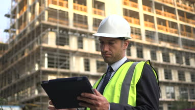 Male architect looking digital tablet at construction site