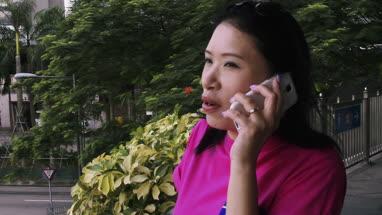 Mature woman talking on mobile phone while standing on footbridge, Hong Kong, China