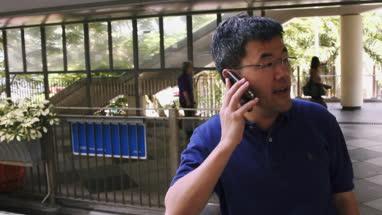 Mature man talking on mobile phone while standing near footbridge, Hong Kong, China