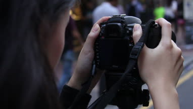 Woman taking photo with digital single-lens reflex camera in Fa Yuen Street Market at Hong Kong, China