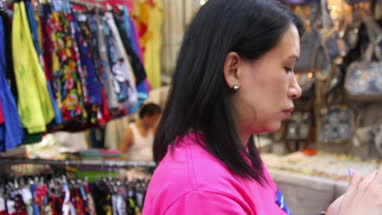 Mature woman talking on mobile phone while standing in Fa Yuen Street Market, Hong Kong, China