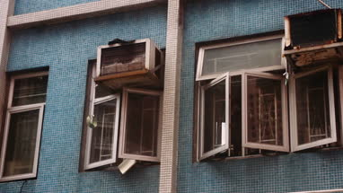 Exterior of house with damaged windows and air conditioner in Hong Kong, China