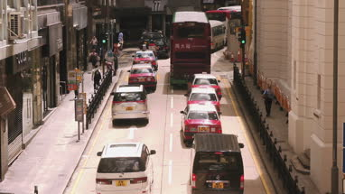 View of traffic and pedestrian walking on pavement in Hong Kong, China