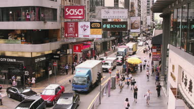 View of city with shops and people walking on street in Hong Kong, China