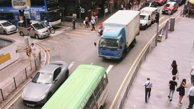 People walking on pavement and vehicle moving on road in Hong Kong city, China