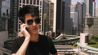 Young man talking on mobile phone, modern buildings in background, Hong Kong, China