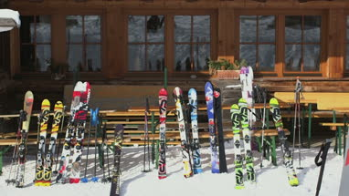 Arranged ski and ski poles outside wooden house
