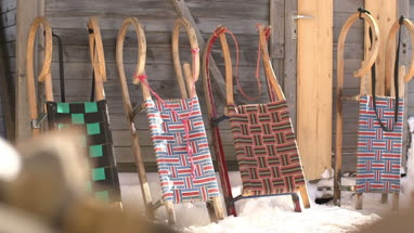 Arranged sledges in snow outside wooden house
