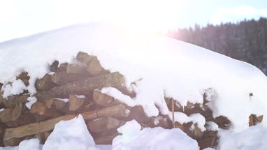 Snow covered firewood stack in winter