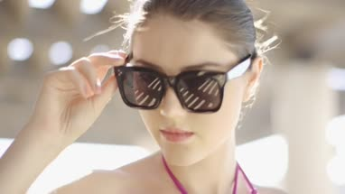 Young adult looking over sunglasses to camera
