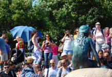 Die kleine Meerjungfrau in Kopenhagen von hinten, davor ganz viele Menschen