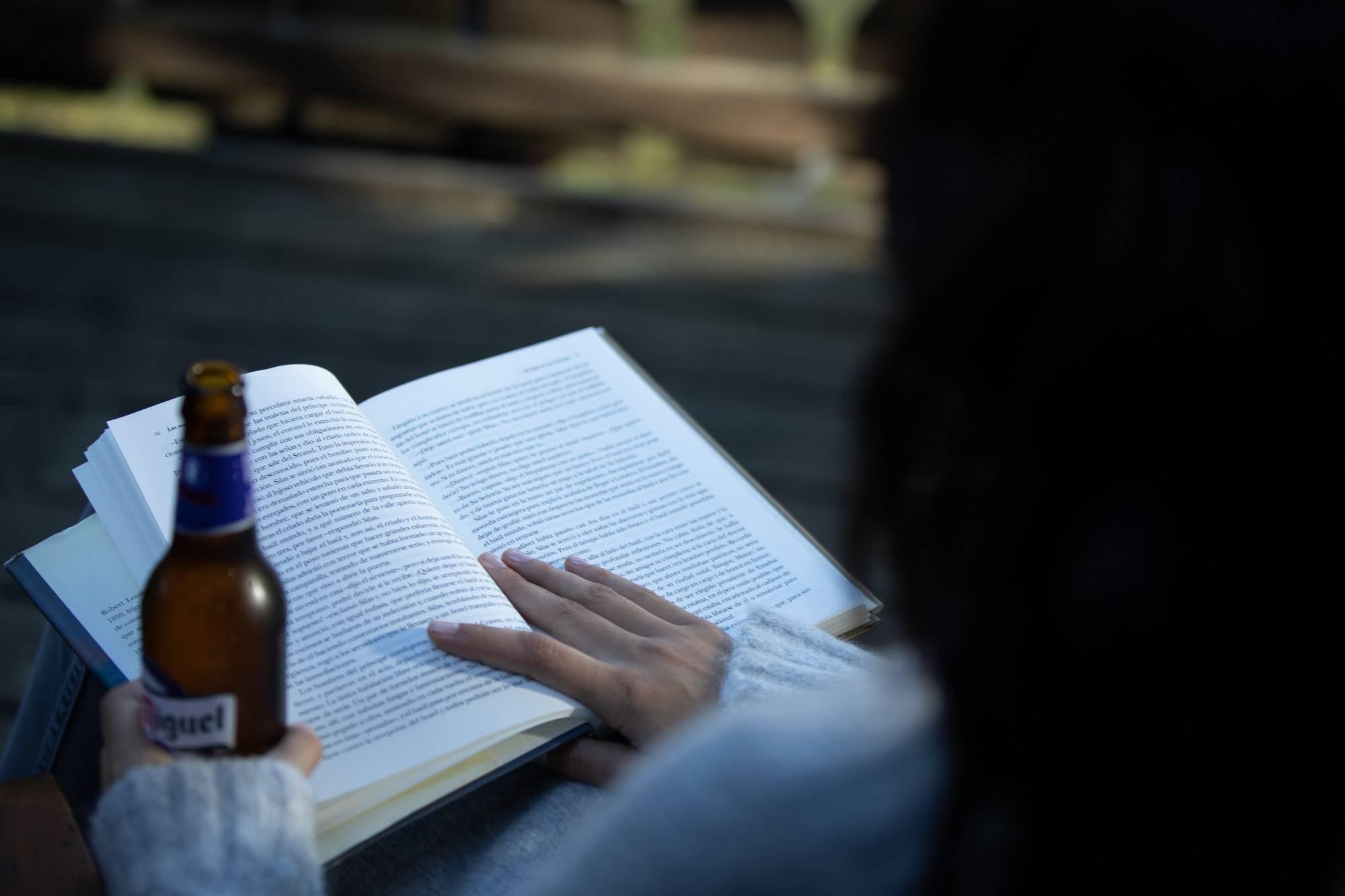 chica bebiendo San Miguel 0,0 mientra lee
