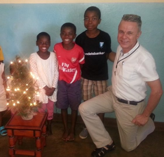 charlie with annies house in Malawi