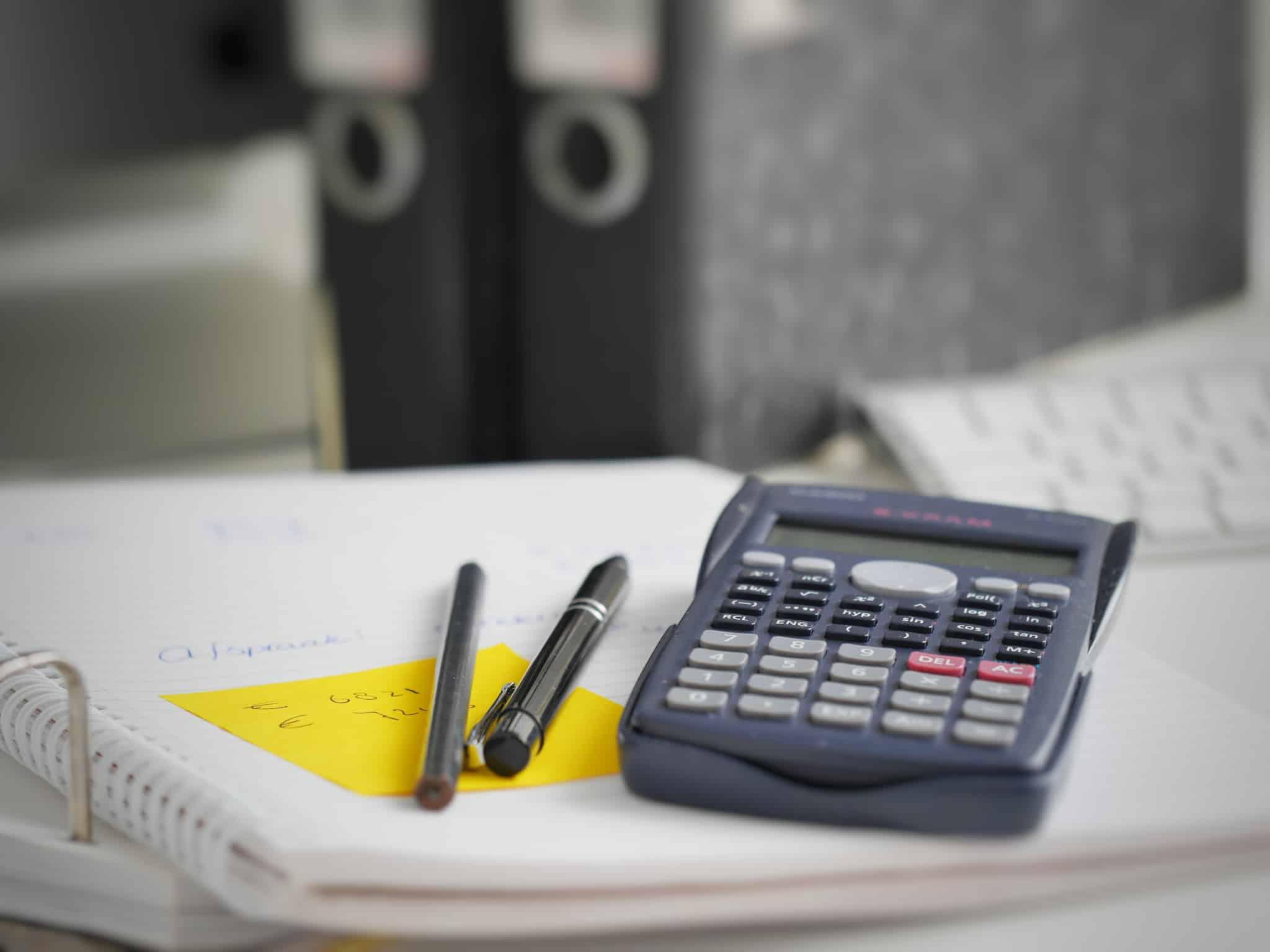 calculadora em cima de papeis de um dossier