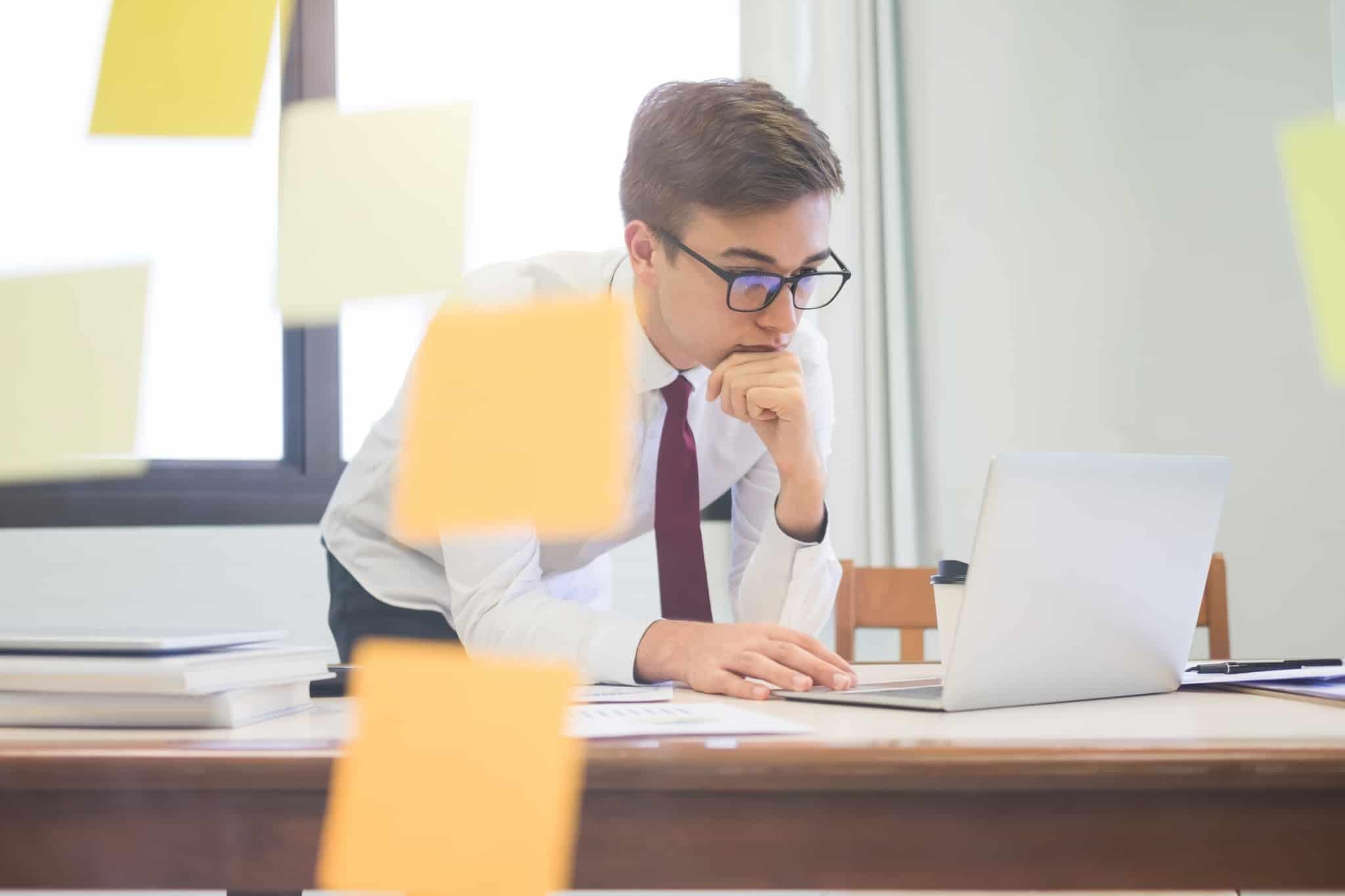 jovem de gravata e com óculos analisa no computador