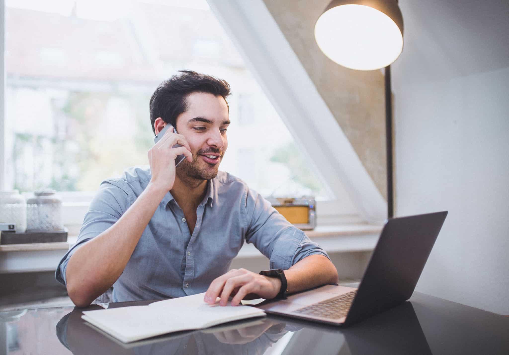 Empresário-individual-a-trabalhar-no-portatil-e-ao-telemovel