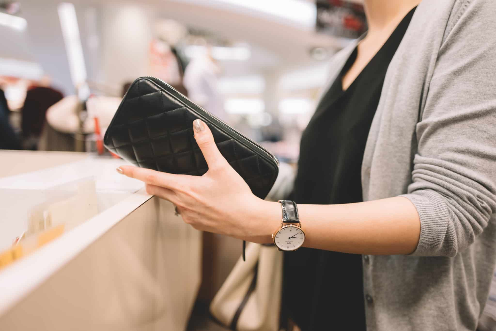 mulher com carteira preta na mão