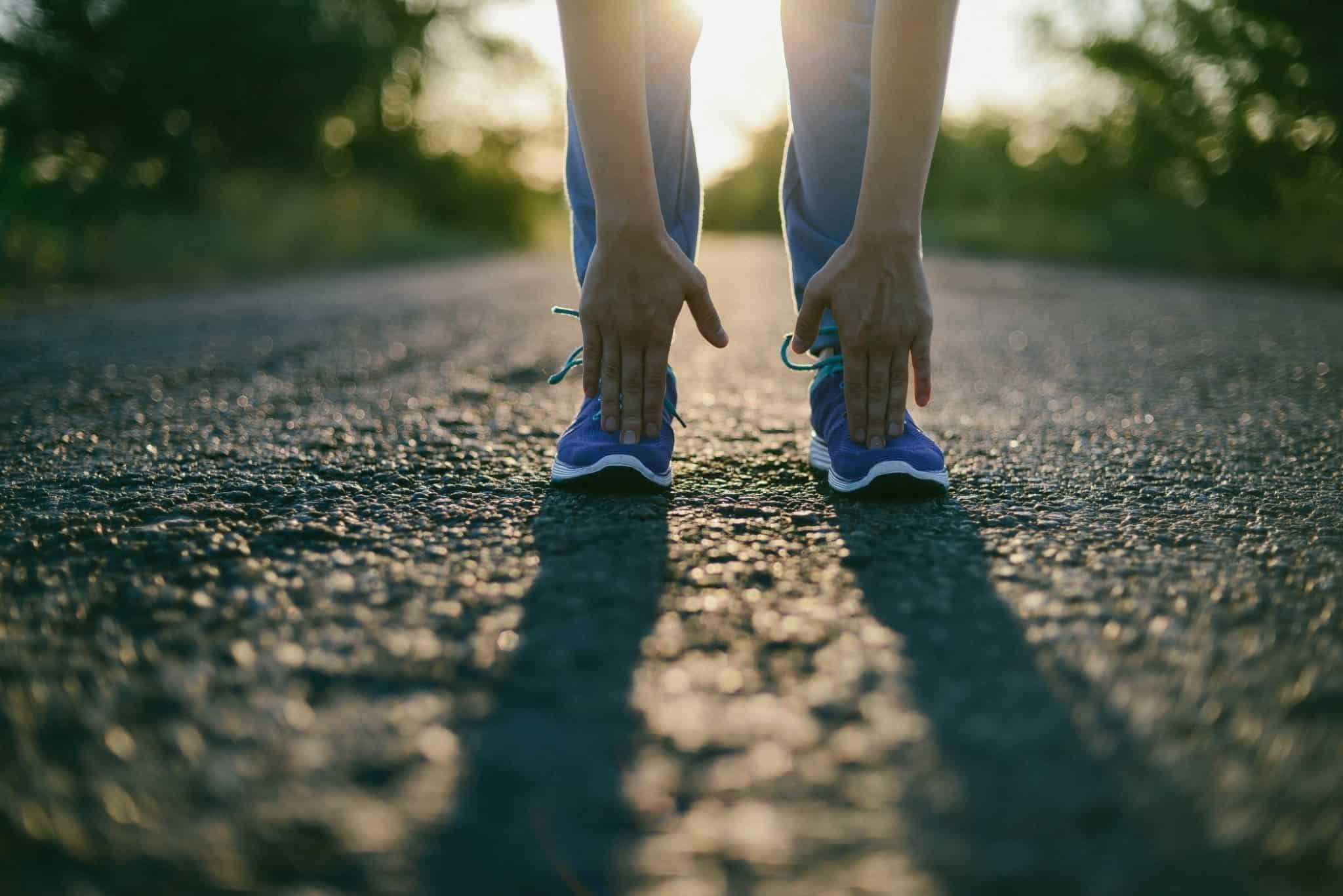 rapariga com tenis a alongar as pernas pronta para correr
