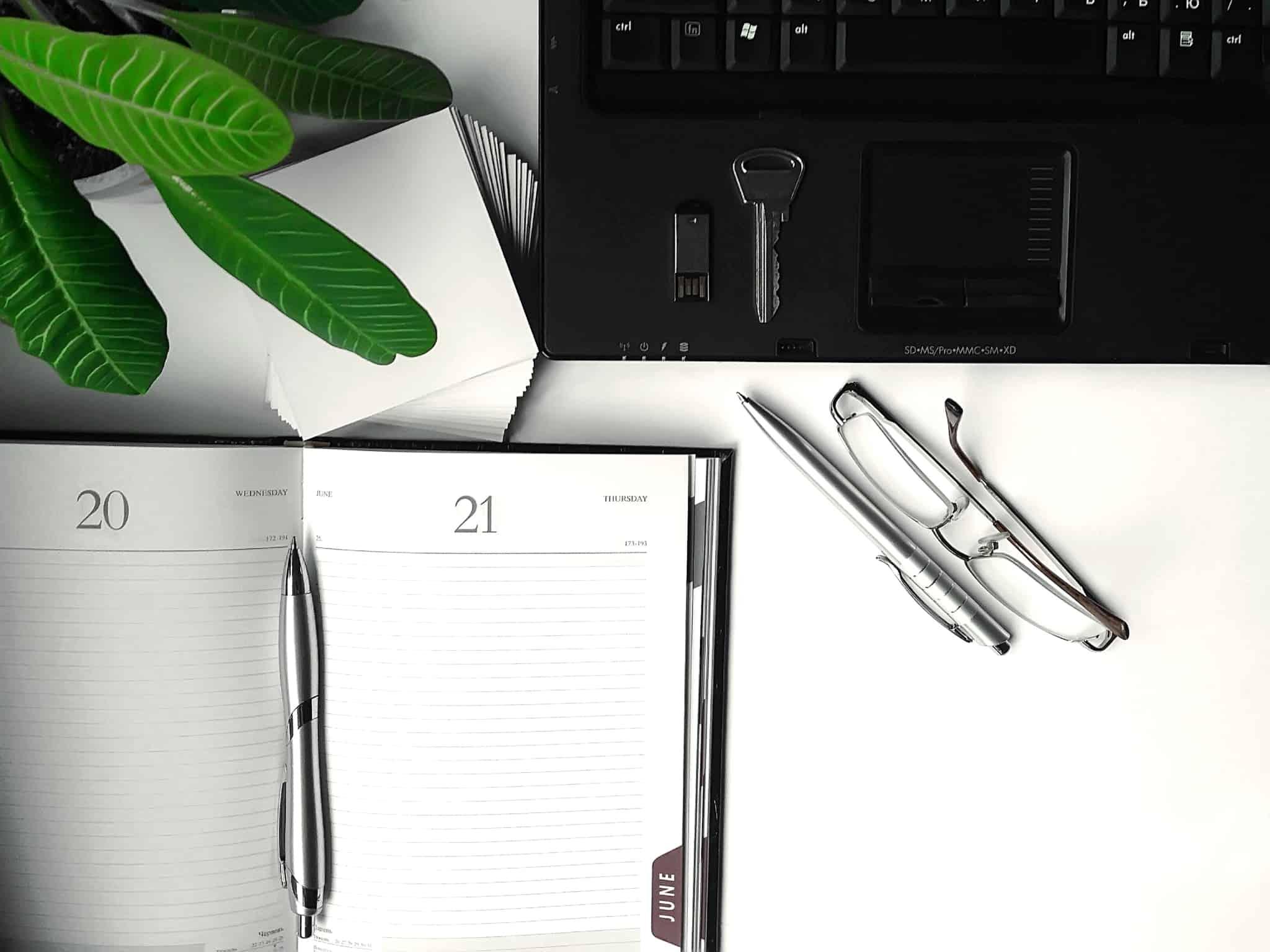agenda aberta no dia 20 e 21 com um computador ao lado, óculos e caneta