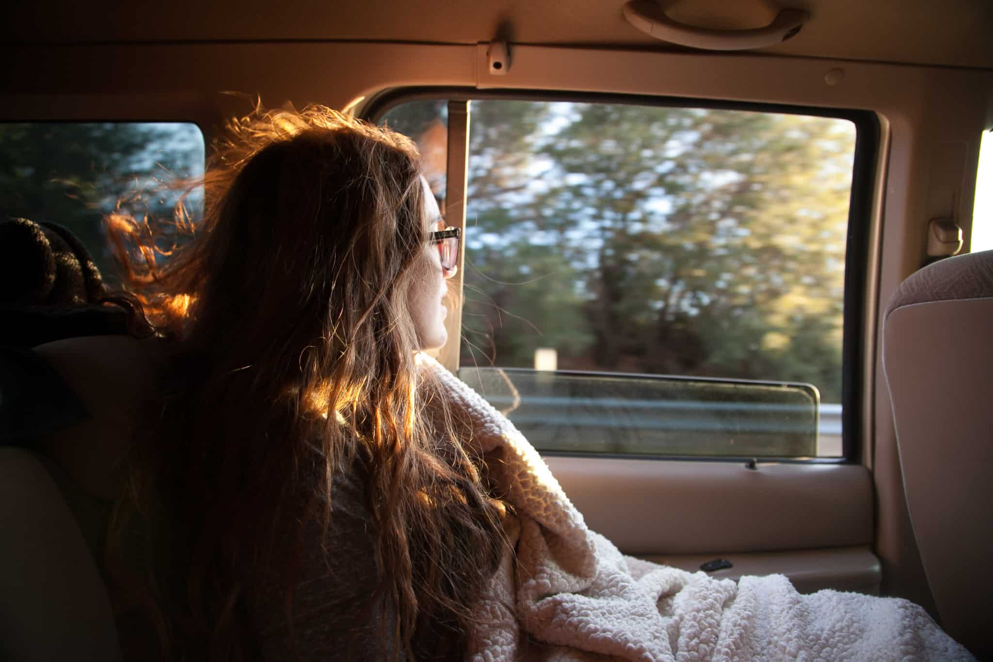 rapariga loira no banco de tras de um carro com a janela aberta