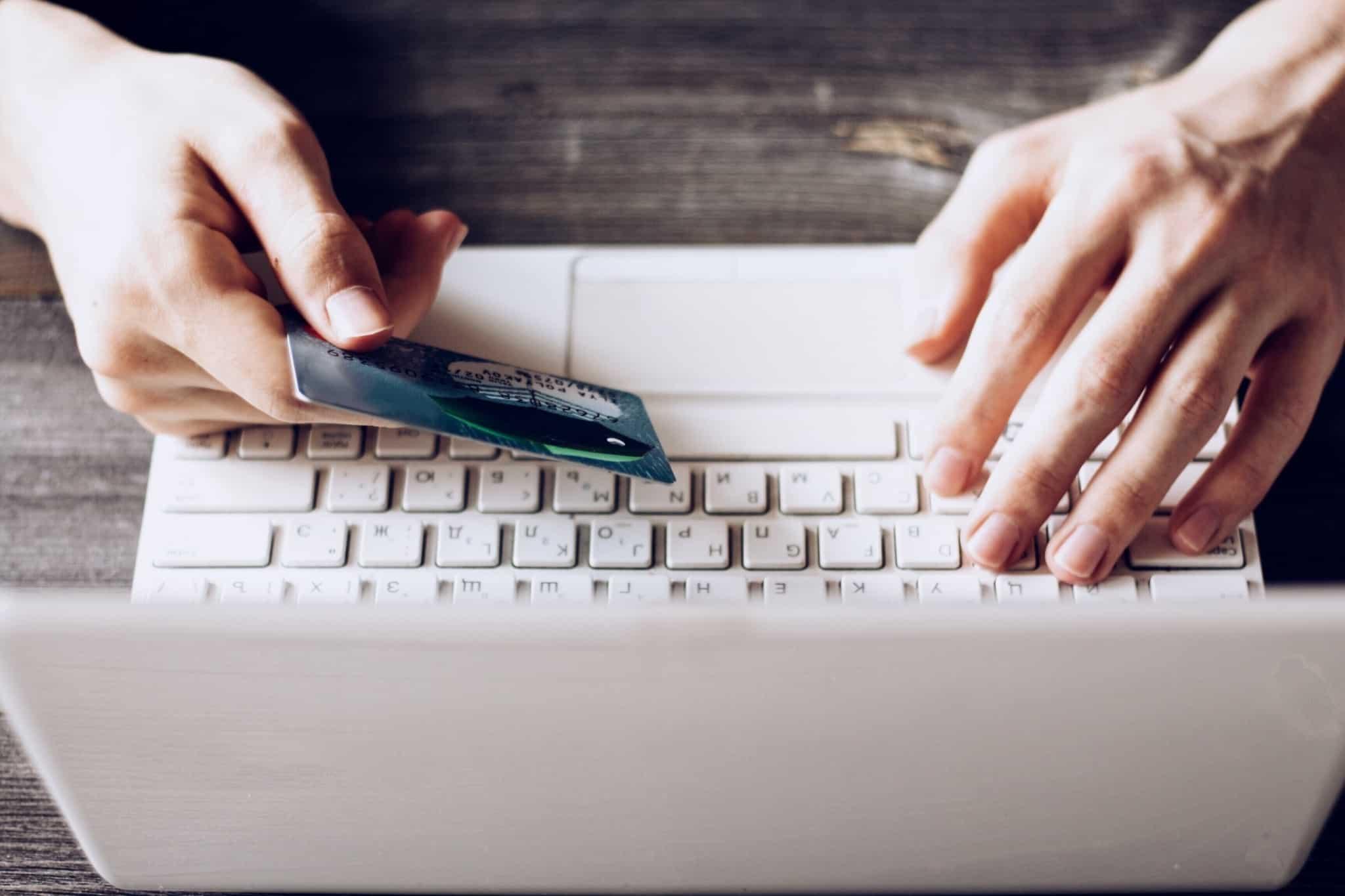 pessoa com o portatil branco e o cartão de crédito na mão direita