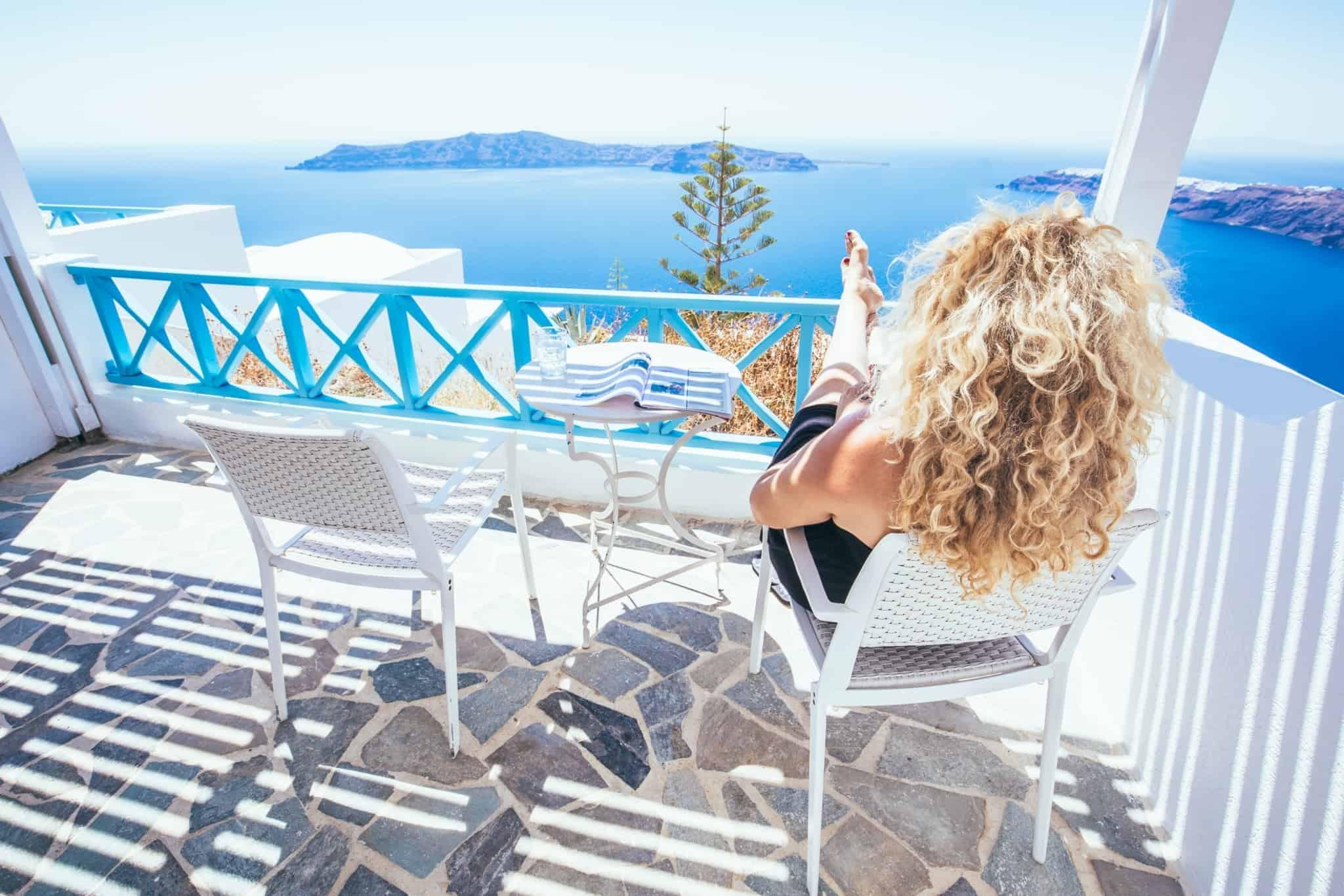 mulher loira sentada na varanda numa ilha grega