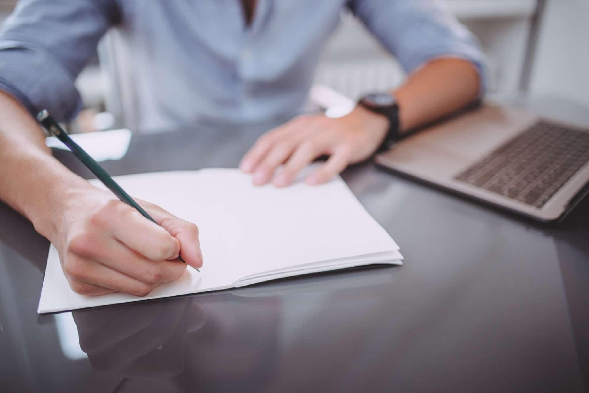 homem tira notas com lápis em caderno branco