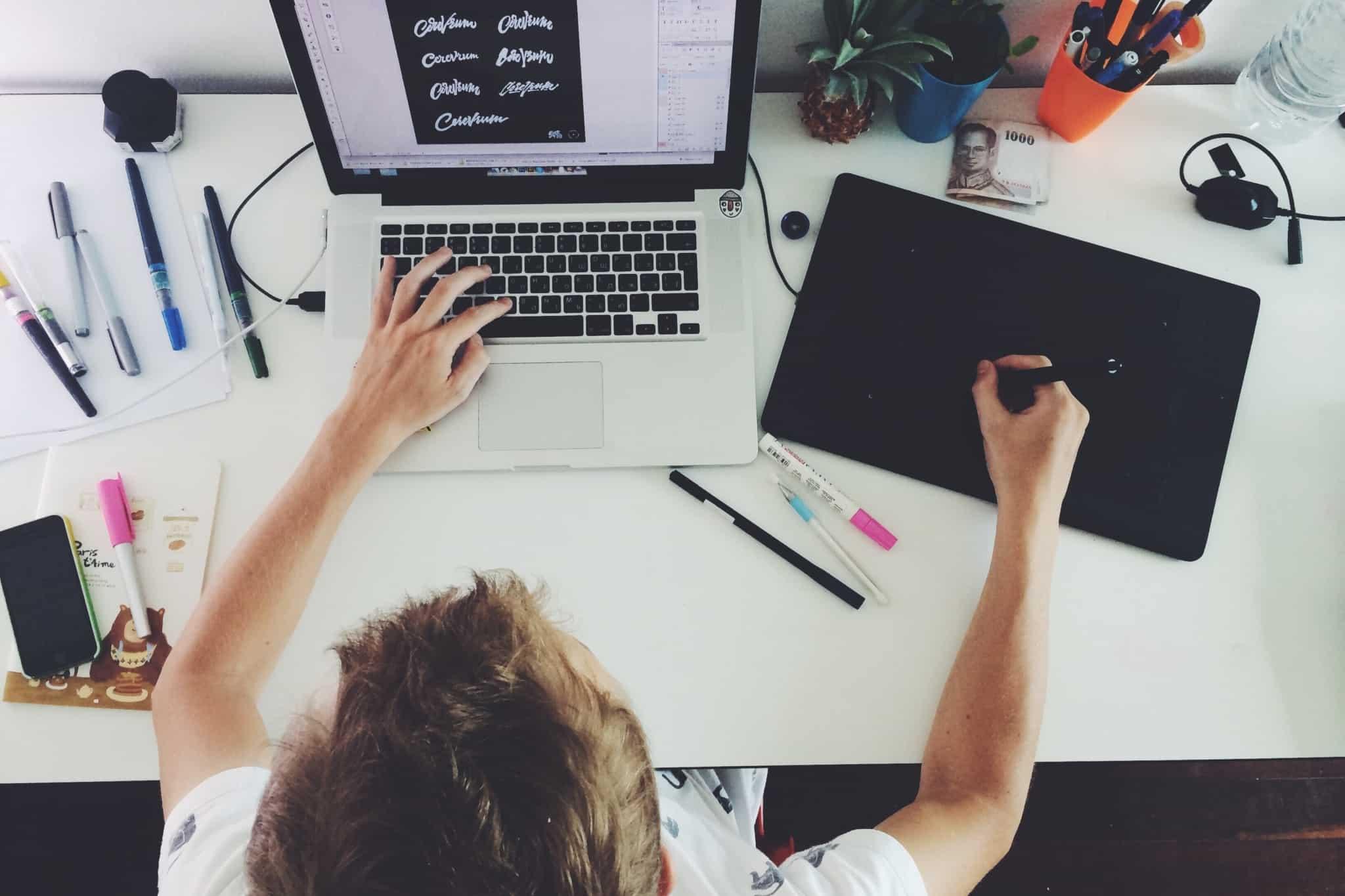 designer faz tipos de letras no portatil e com uma mesa gráfica