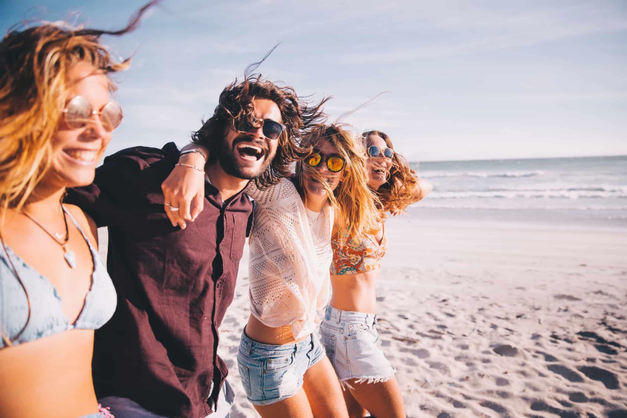 grupo de amigos na praia sorridentes
