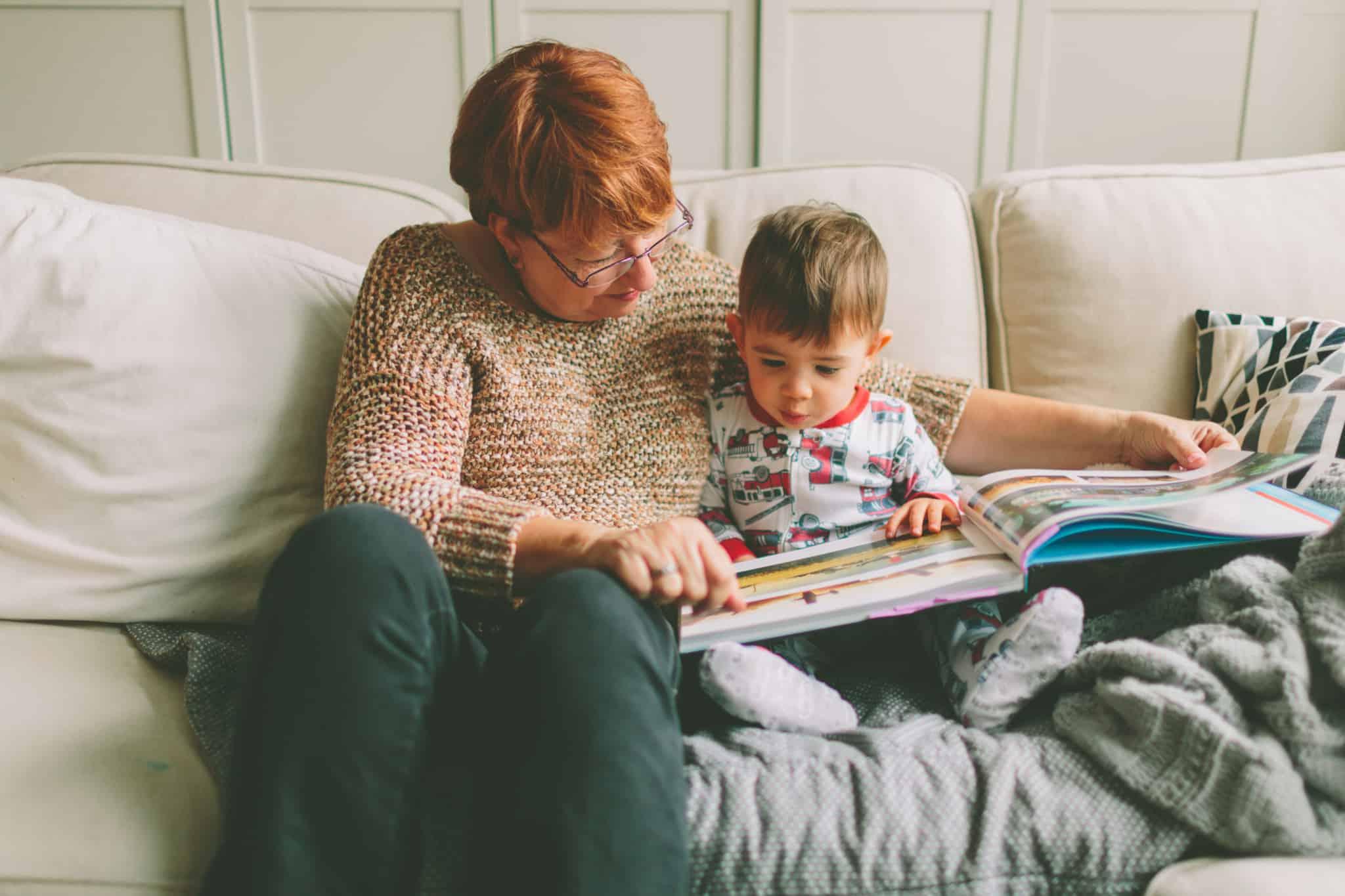 avó ruiva a ler história com o neto no sofá