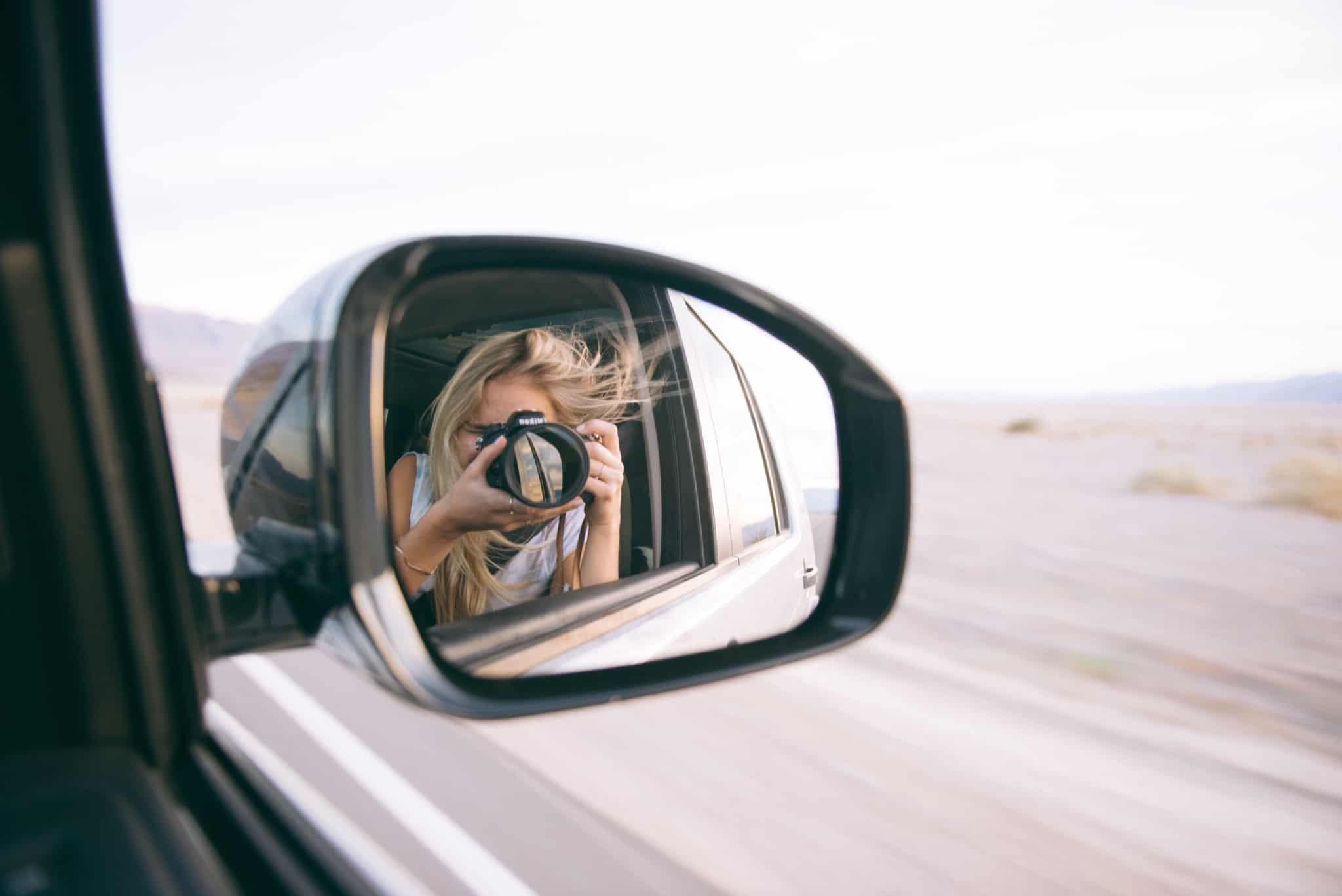 rapariga a tirar foto ao retrovisor de um carro