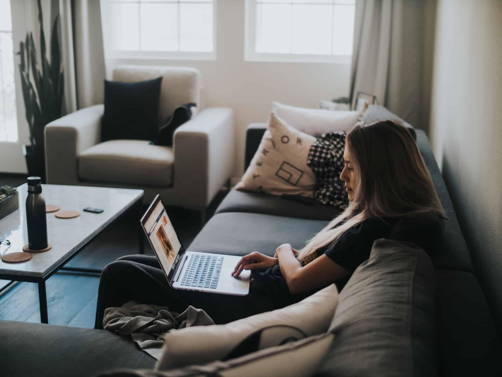 rapariga sentada no sofá com computador no colo