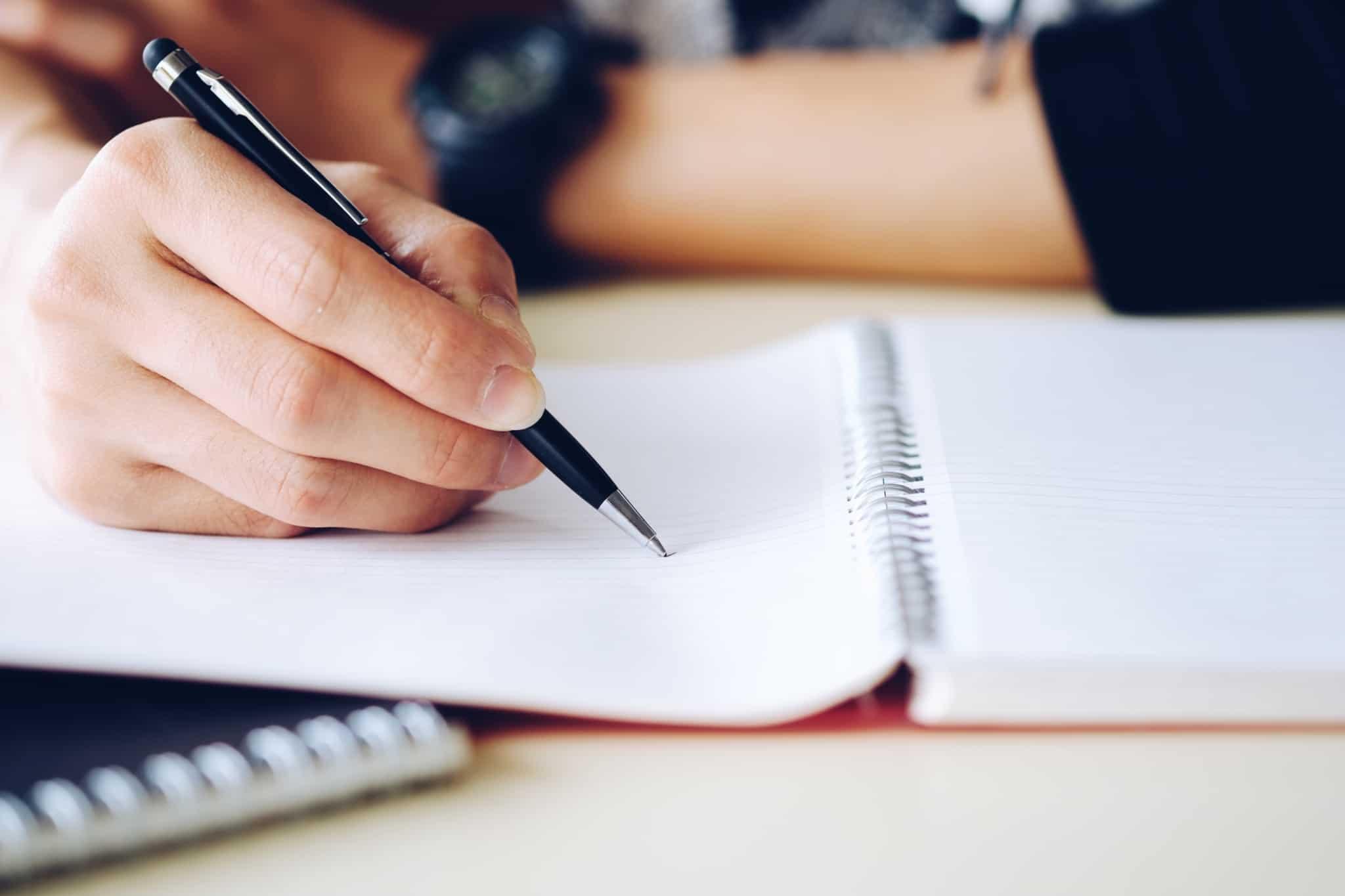 escrever com uma caneta num caderno de argolas