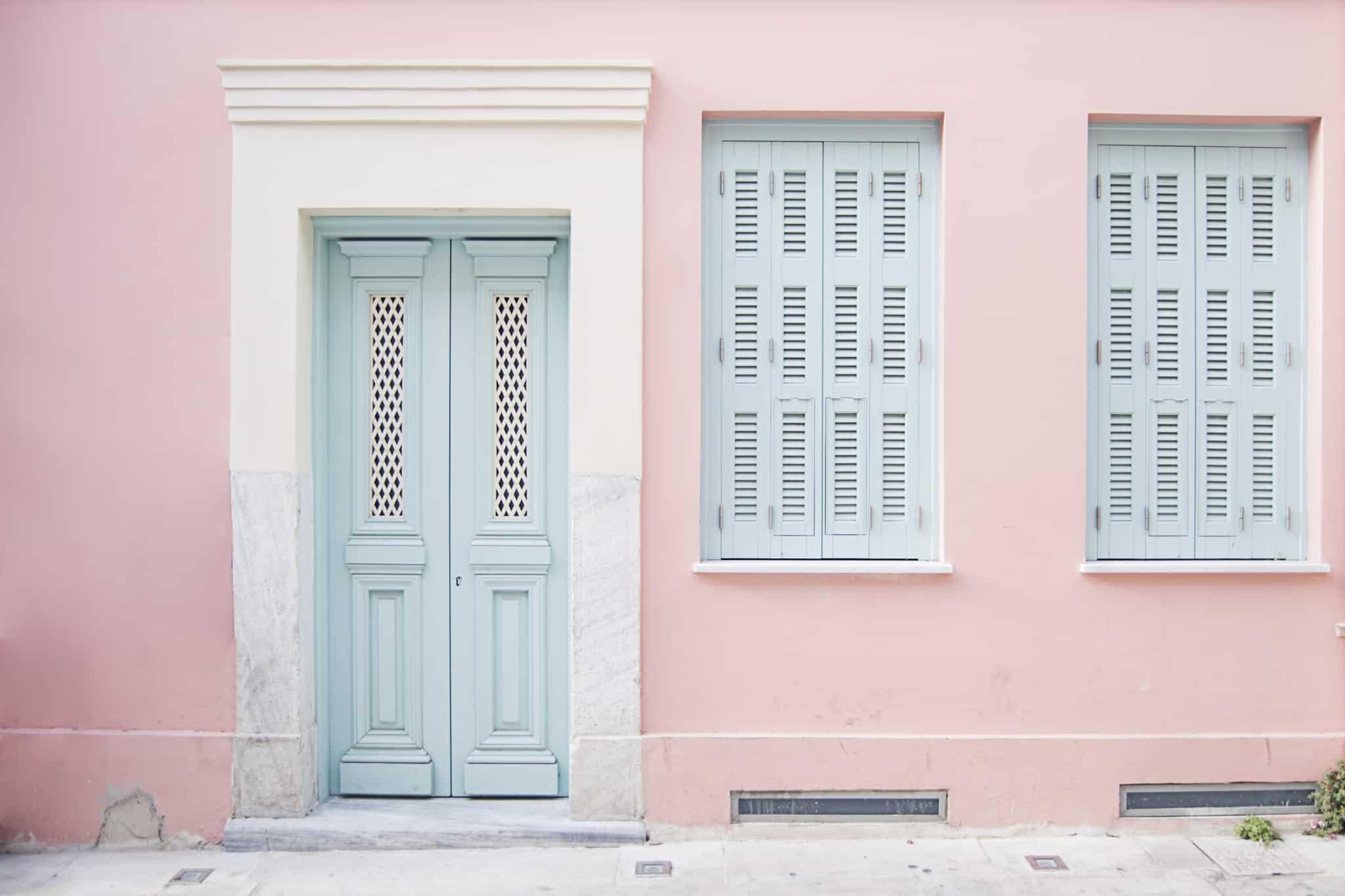 porta e duas janelas de uma casa cor de rosa