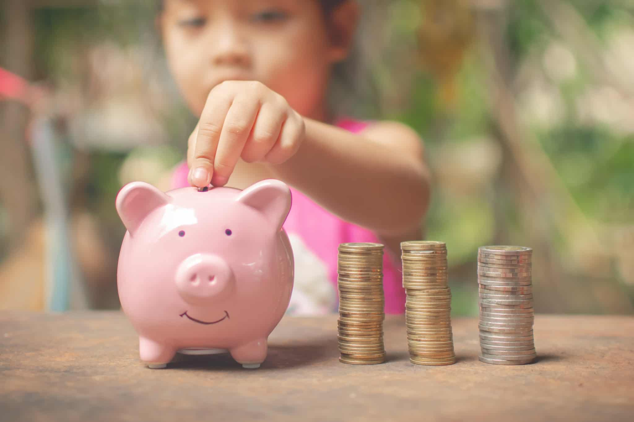 criança a colocar moedas num porquinho mealheiro cor de rosa