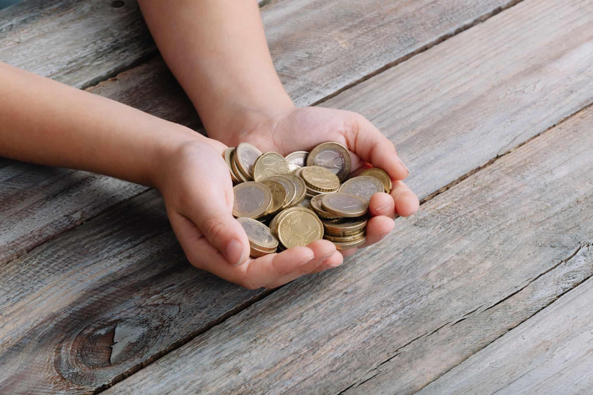 criança com as duas maos cheias de moedas de euro