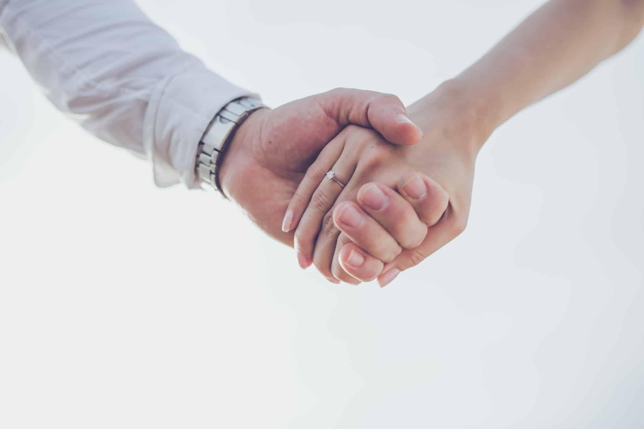 casal de maos dadas no dia do casamento