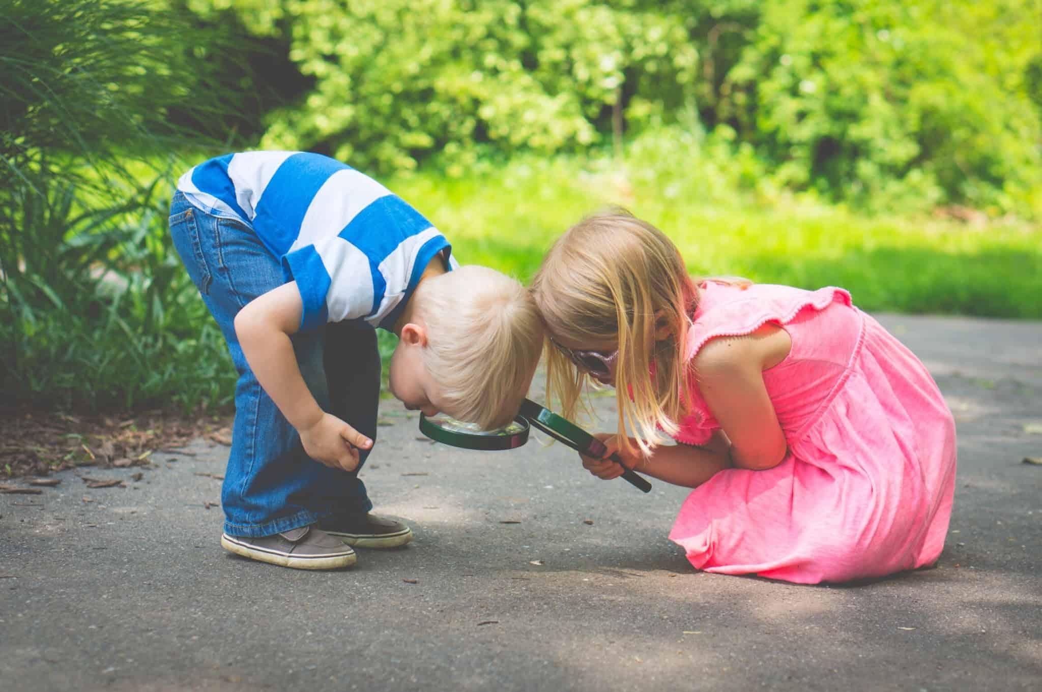 duas crianças a olhar para o chão com lupas