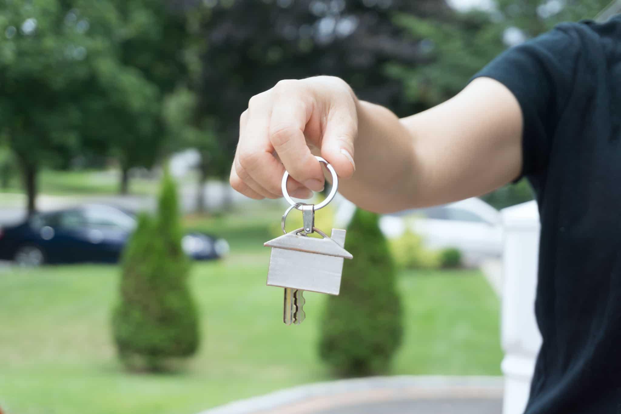 Homem a segurar em porta chaves de uma casa