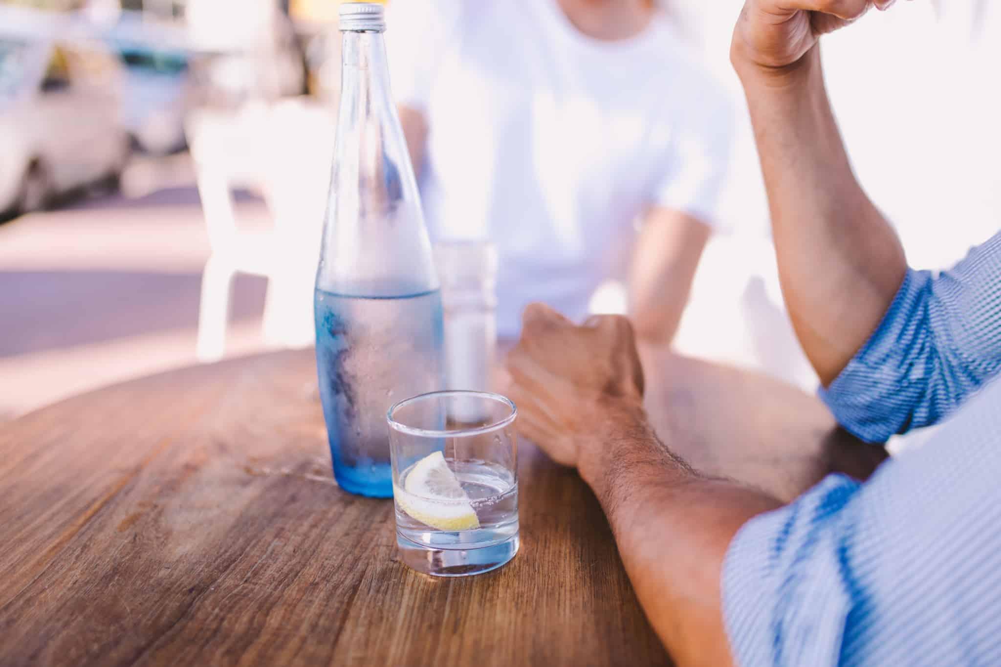 homem a beber copo com água e rodela de limão e uma garrafa de água de vidro