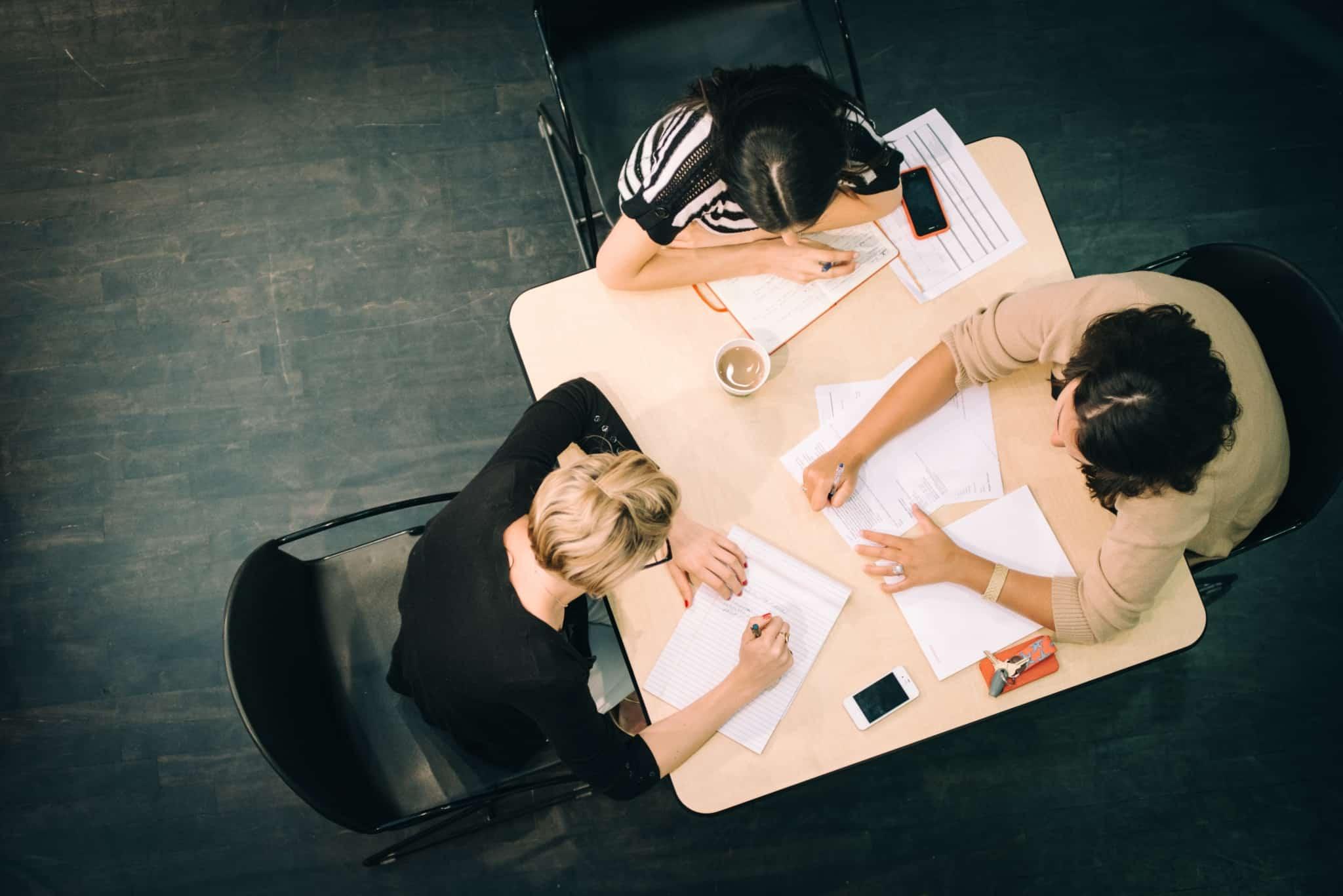reuniao de equipa com três pessoas numa mesa quadrada