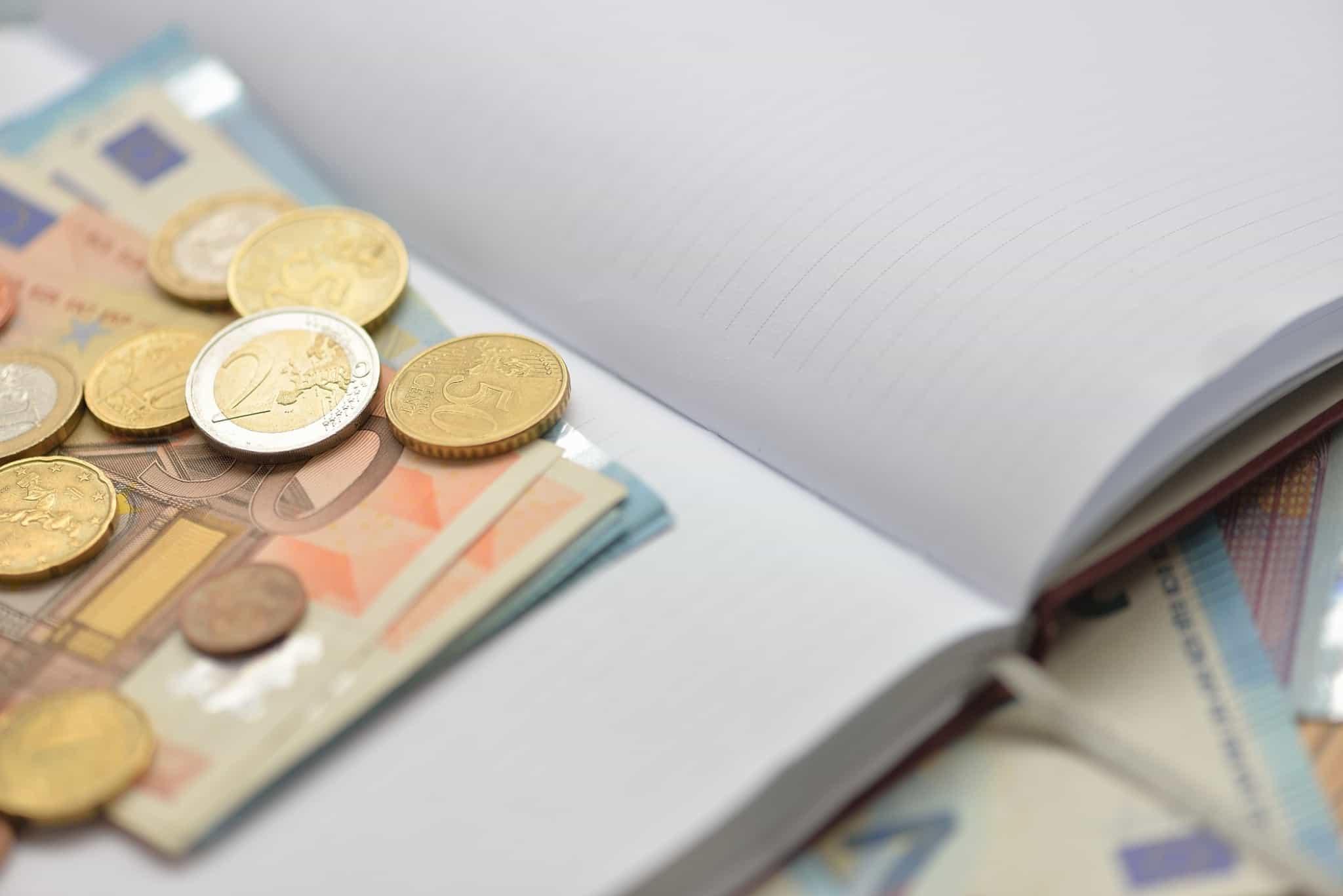 caderno aberto com moedas lá dentro