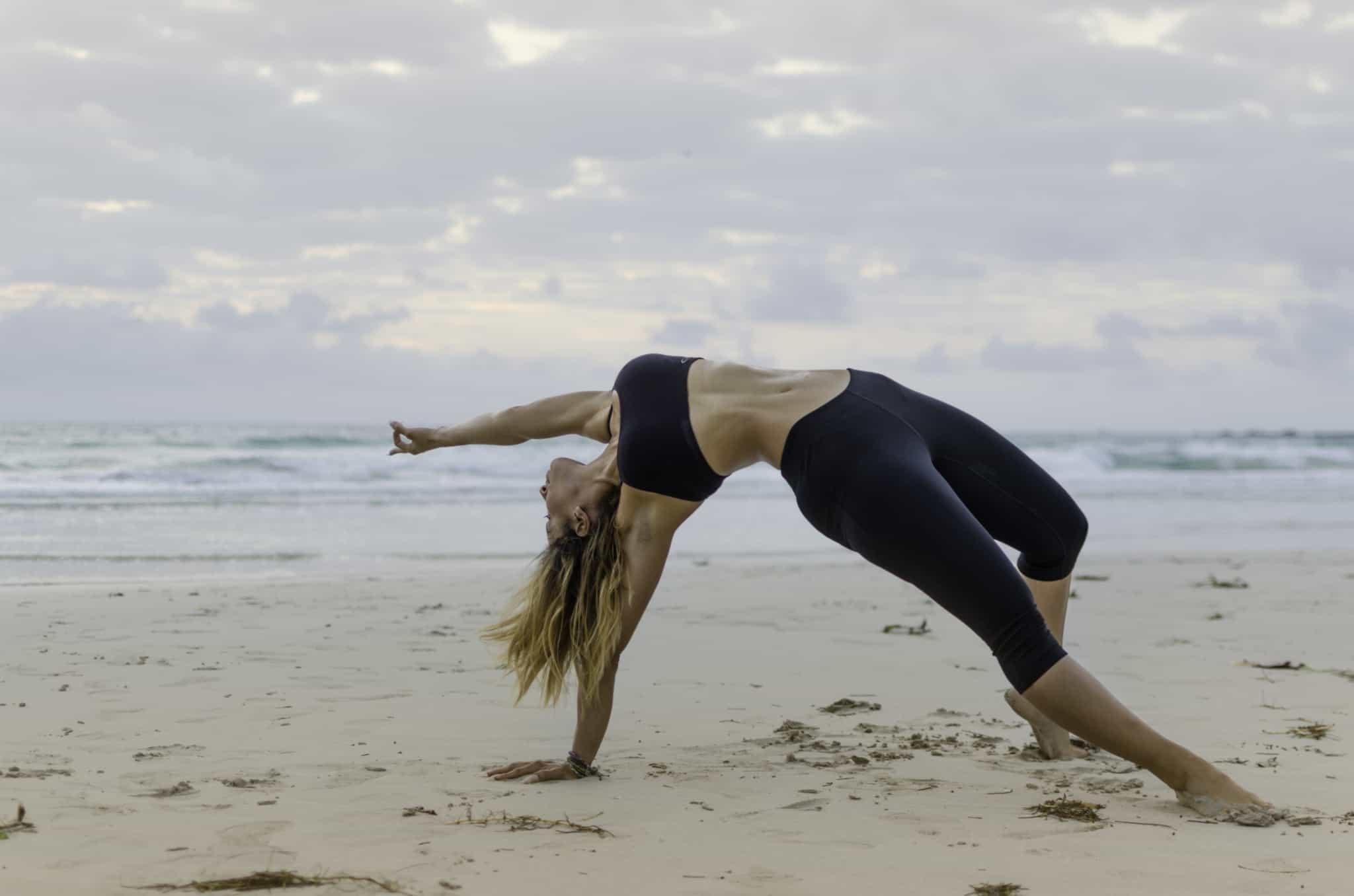 rapariga em posiçãod e yoga na praia