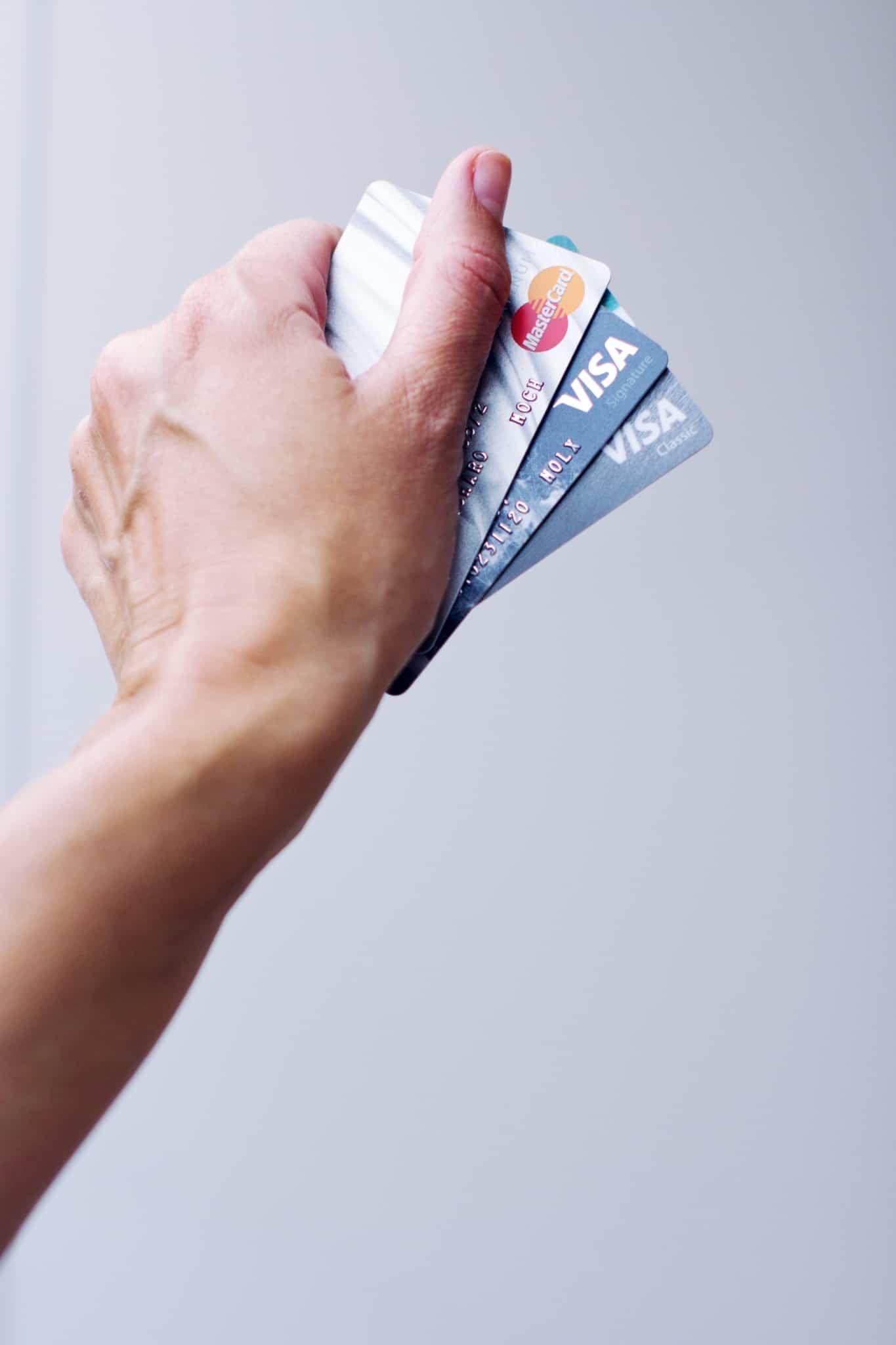 mão a segurar dois cartões visa e um cartão mastercard